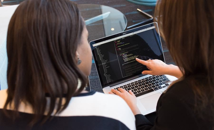 Two women going through source code together
